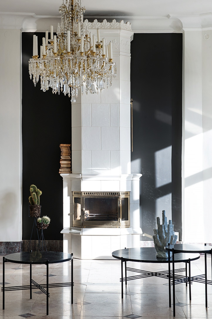 scandinavian fireplace with white tiles on black wall and with crystal chandelier