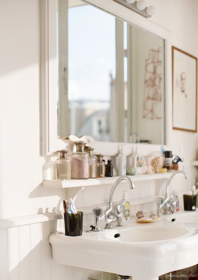 Old Pedestal Sink with Oval Basin, Wood Shelf On Wall Scattered With Perfume Bottles, Cup with Toothbrushes, Beadboard on half of wall, chrome faucets- via housebeautiful