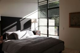 via my scandanavian home - dark grey upholstered headboard with chinese night stand, mixed color linen coverlet and sheets, sun steaming in black glazed floor to ceiling windows