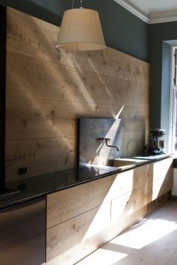Wide Plank Wood Wall in Modern Rustic Kitchen with Slate Counter Tops and Wall Mounted Faucet In Stone Slab -via coco lapine