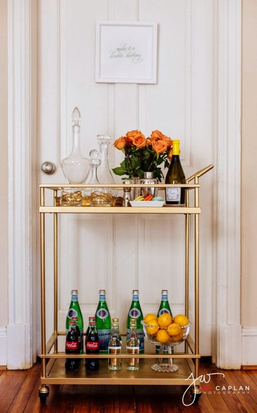 jw caplan photo gold bar cart with bowl of oranges, coral roses, glass decanters and green glass bottled water
