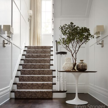 white paneled entry and stairway with tulip table-white and silver vases - mini tree on table- silver wall sconces with fabric shades-carpet stair runner