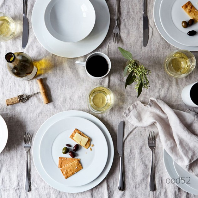 Food 52 Table with linen table cloth and white dishes, cheese and crackers with olives and white wine and coffee