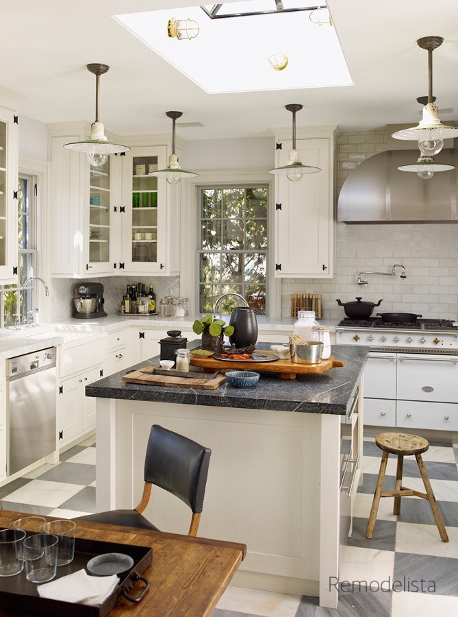 remodelista Kitchen with gray and white checkerboard floor  and wooden stool near center island laid out with food