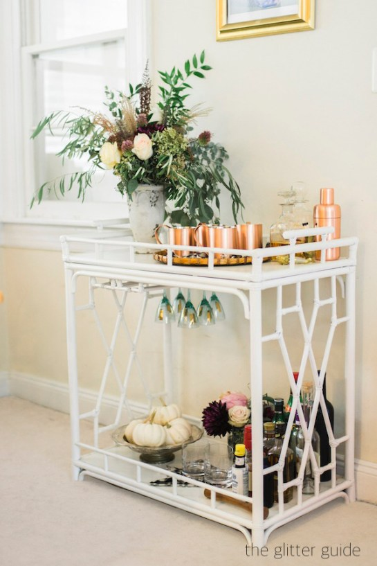 theglitterguide white painted rattan bar car with copper mules, bowl of white pumpkins and vase of greenery
