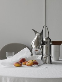 chrome water kitchen, french press coffee on table with white linen cloth, 5 peaches sitting on cloth, soft gray walls in the background, empty water glass next to peaches