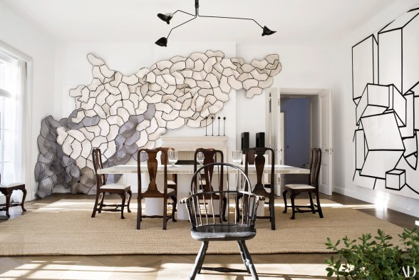architectural digest dining room with large art and mixed chairs with white table sisal area rug