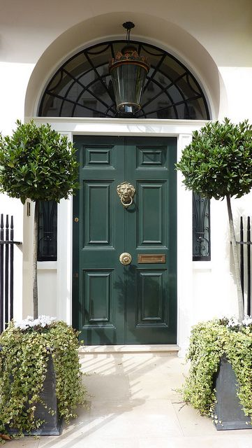 How do you top this leaded glass arched transom? A fantastic green door paint and brass lion door knocker is how! via pinterest