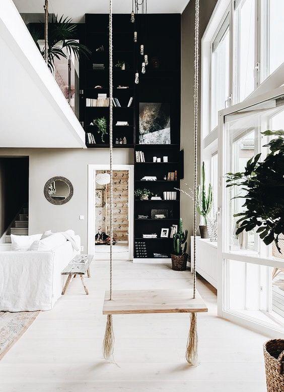 Une balançoire dans le salon black floor to ceiling bookcases