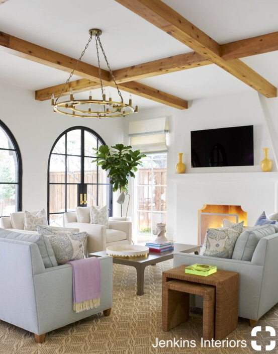jenkins interiors living room with beamed ceiling, stucco fireplace, arched doors