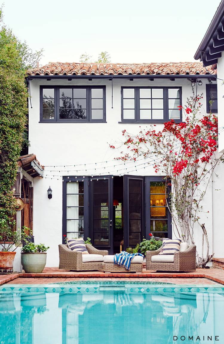 domaine spanish style home -terra cotta tile roof- aqua pool-white stucco walls-black window frames- bougevilla-potted plants-round gutters