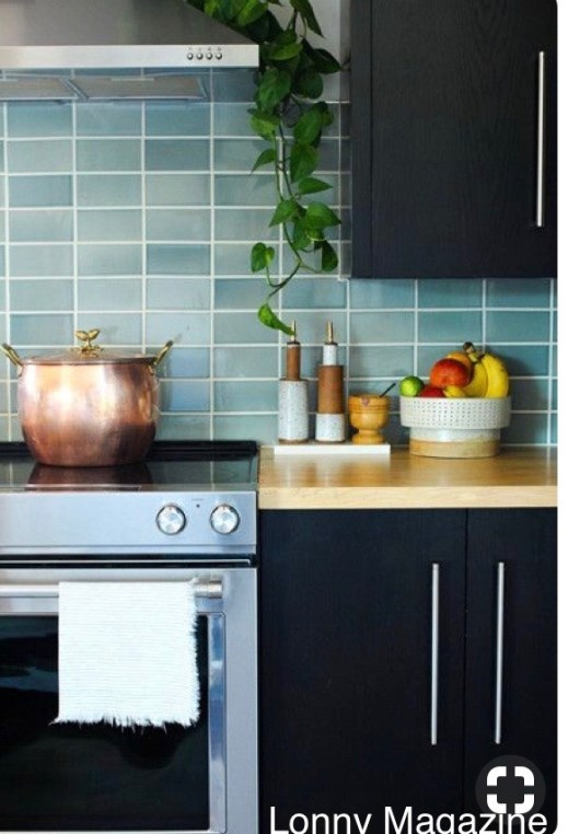 lonny magazine black cabinets-butcher block counter top-blue muted splash tile-copper pot