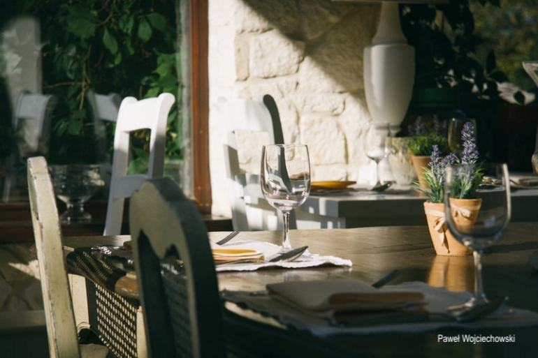 pawel wojoiechowski- indoor dining table brought outside-pots of rosemary-wine glasses sitting in the sun- alfresco dining