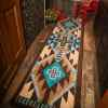 turquoise and brown runner and red chair