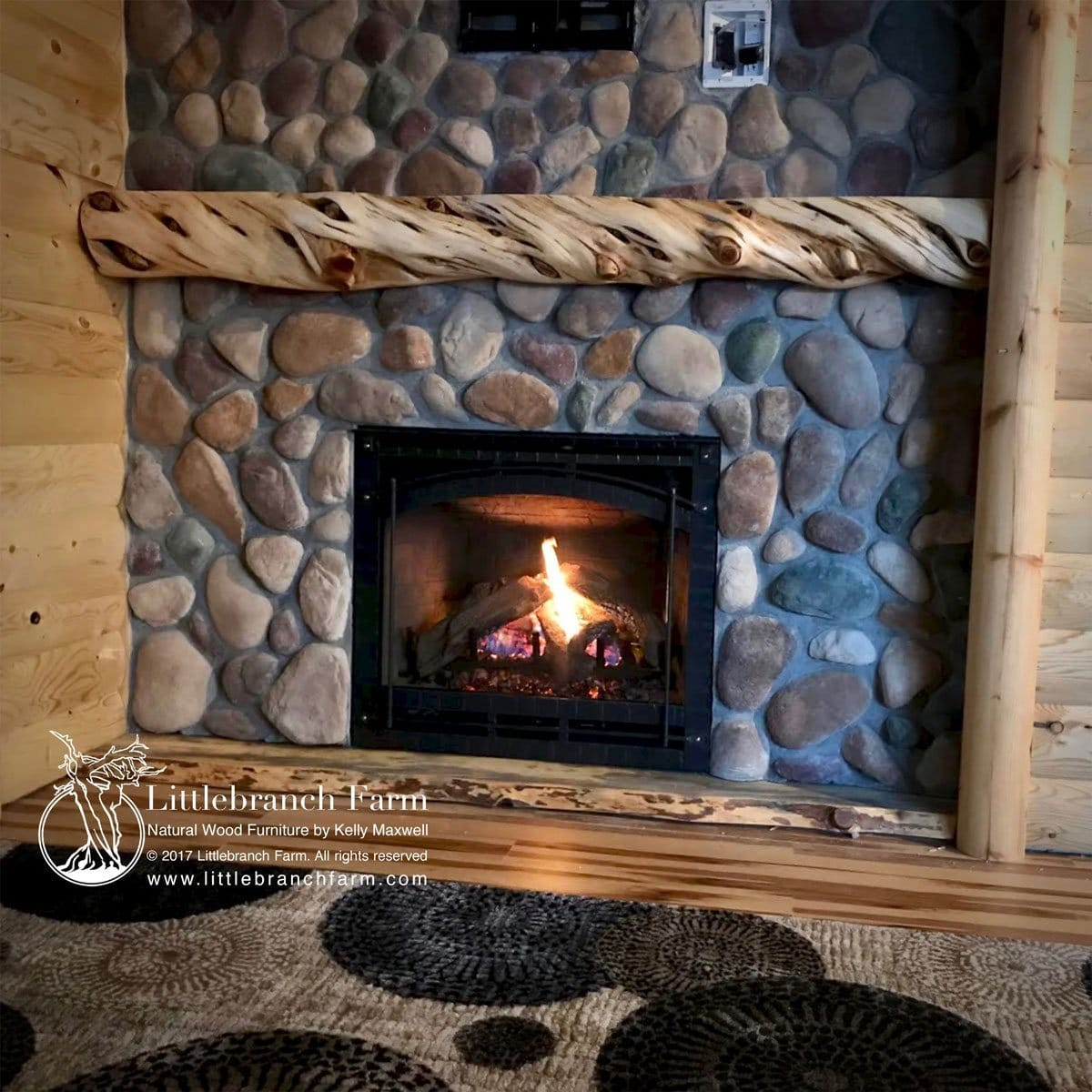 Log mantel on river stone fireplace.
