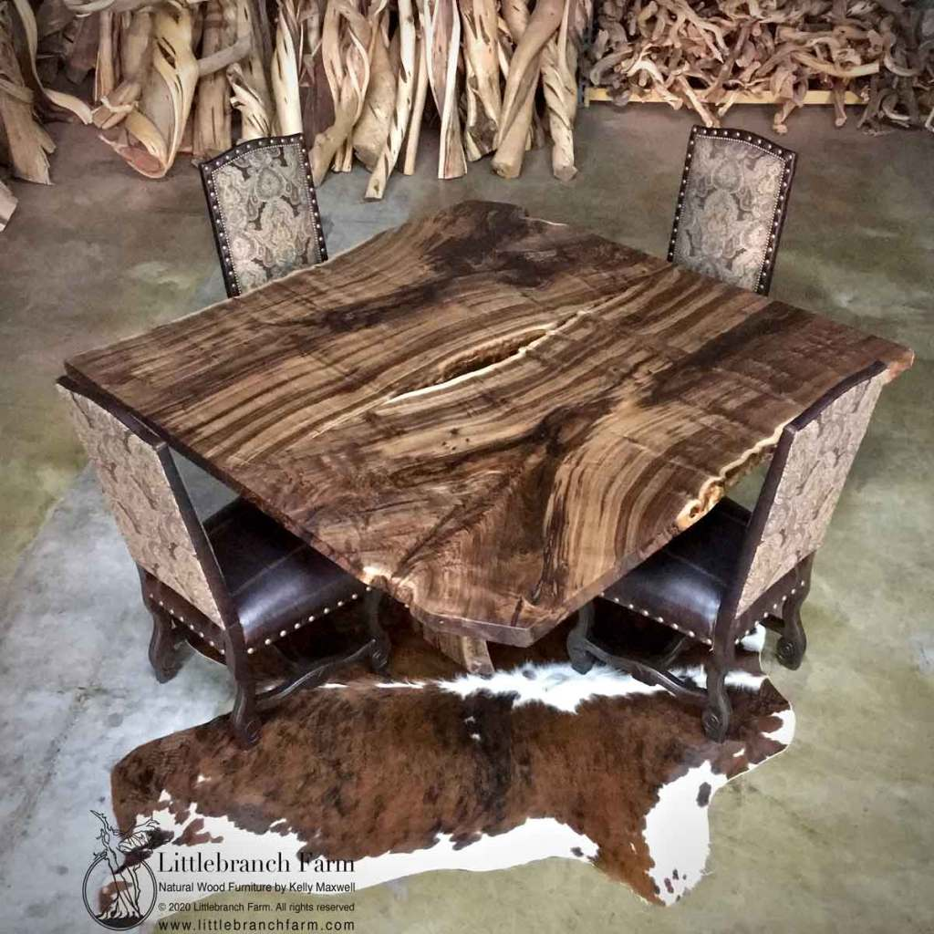 Square live edge table on cow hide rug.