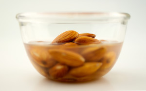 Almonds being soaked in a clear bowl, isolated on white