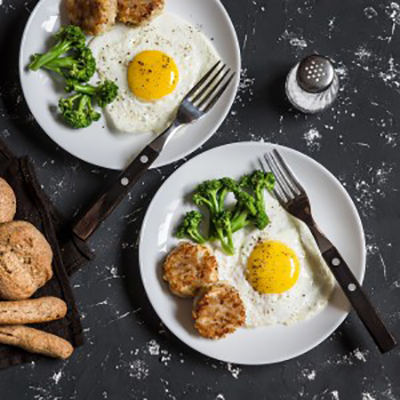 Fried eggs, broccoli, chicken meatballs, homemade whole wheat bread - tasty simple dinner. On a dark background, top view