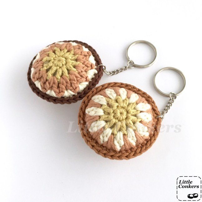 Round crocheted keychains in browns, yellows and neutrals.