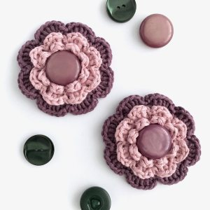 Purple and pink crocheted flower brooches with button centres