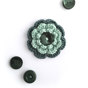 Hand-crocheted green brooch with upcycled buttons