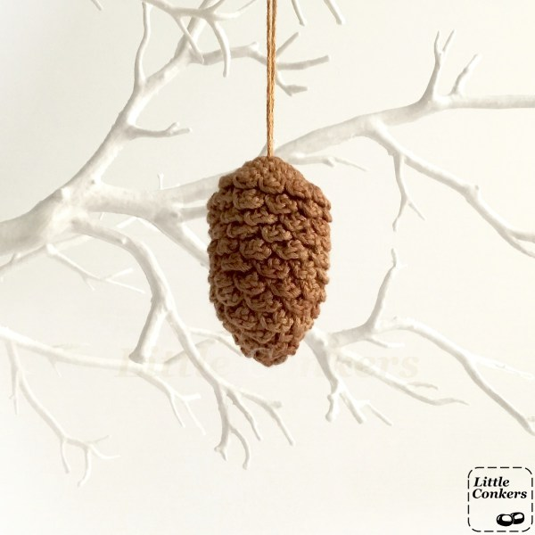 Crocheted pine cone ornament hanging on a twig tree