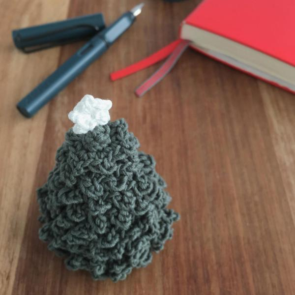 Miniature crocheted Christmas tree with white star on a wooden table