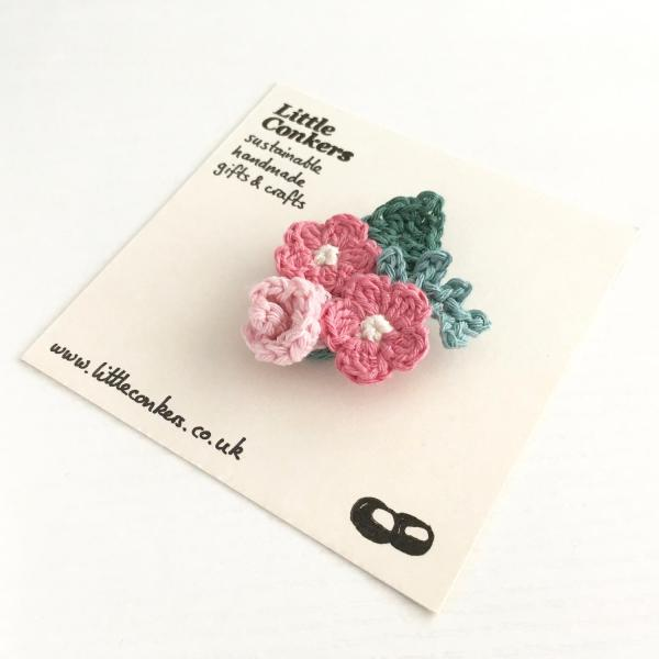 Crocheted bouquet brooch with pink flowers and green leaves