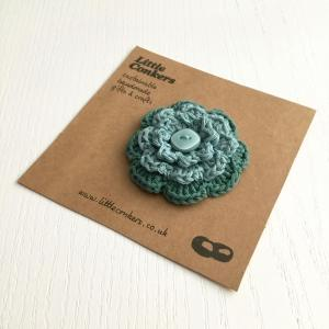 Crocheted flower brooch in teal green with upcycled button