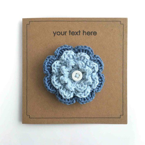 Blue crocheted flower brooch on kraft greetings card