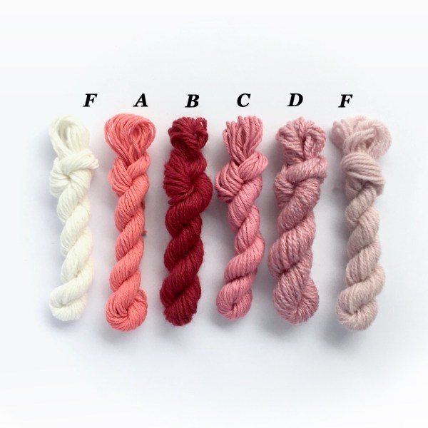 Mini yarn skeins in shades of red and pink