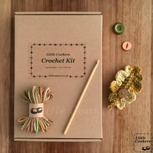 Crochet kit in brown cardboard box with green and gold wool and buttons