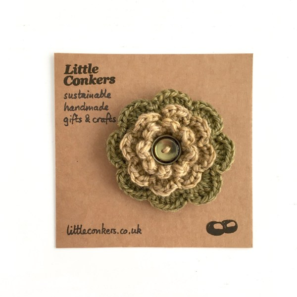 Hand-crocheted flower brooch in olive green and gold with button centre