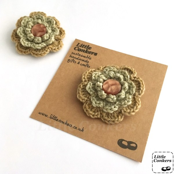 Hand-crocheted flower brooch in gold and pale green with amber button