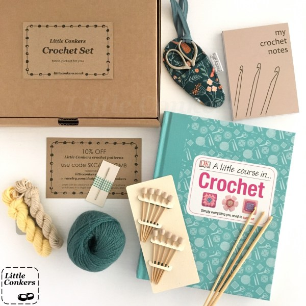 Crochet hooks, book, yarn, notepad and scissors