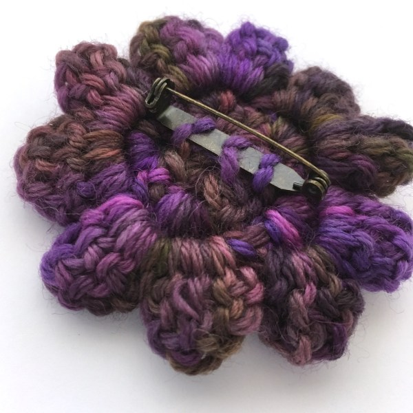 Back of a crocheted flower brooch in purple wool