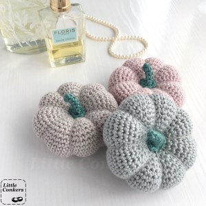 Three mini crocheted pumpkin ornaments in pale pink, pale grey and duck egg blue.