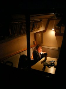 Reading in the cabin of our tiny house, S/V Moonrise