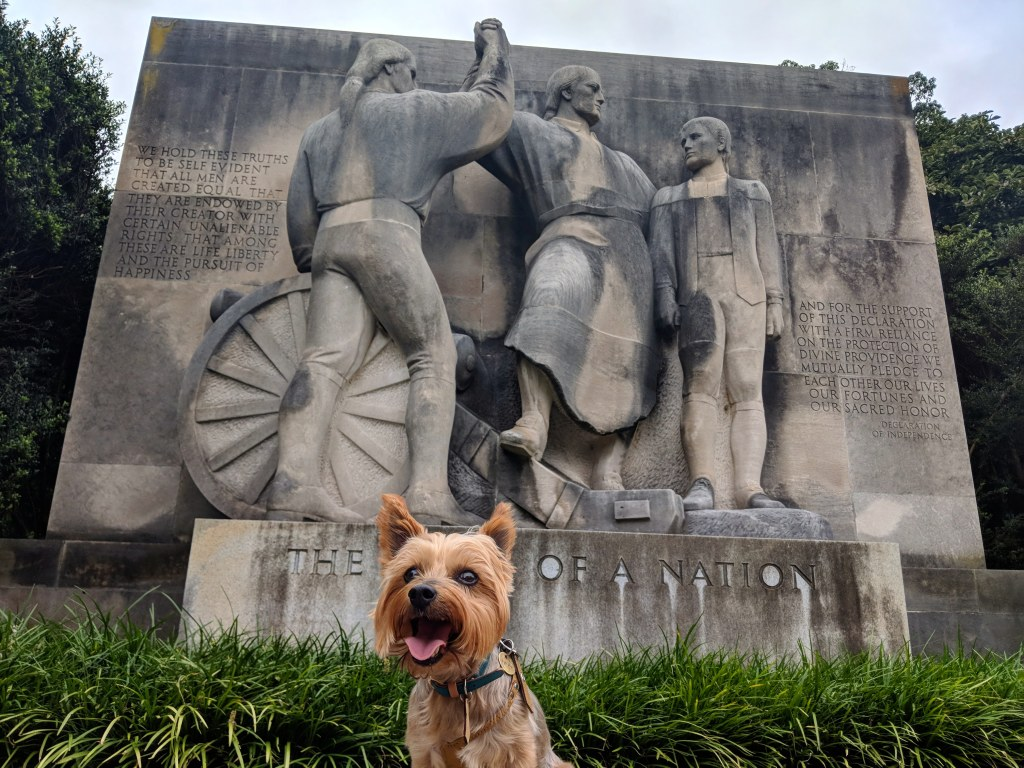 "A small dog stands in front of a large statue in Philadelphia titled ""The Birth of a Nation."" The dog is blocking the word ""birth."""