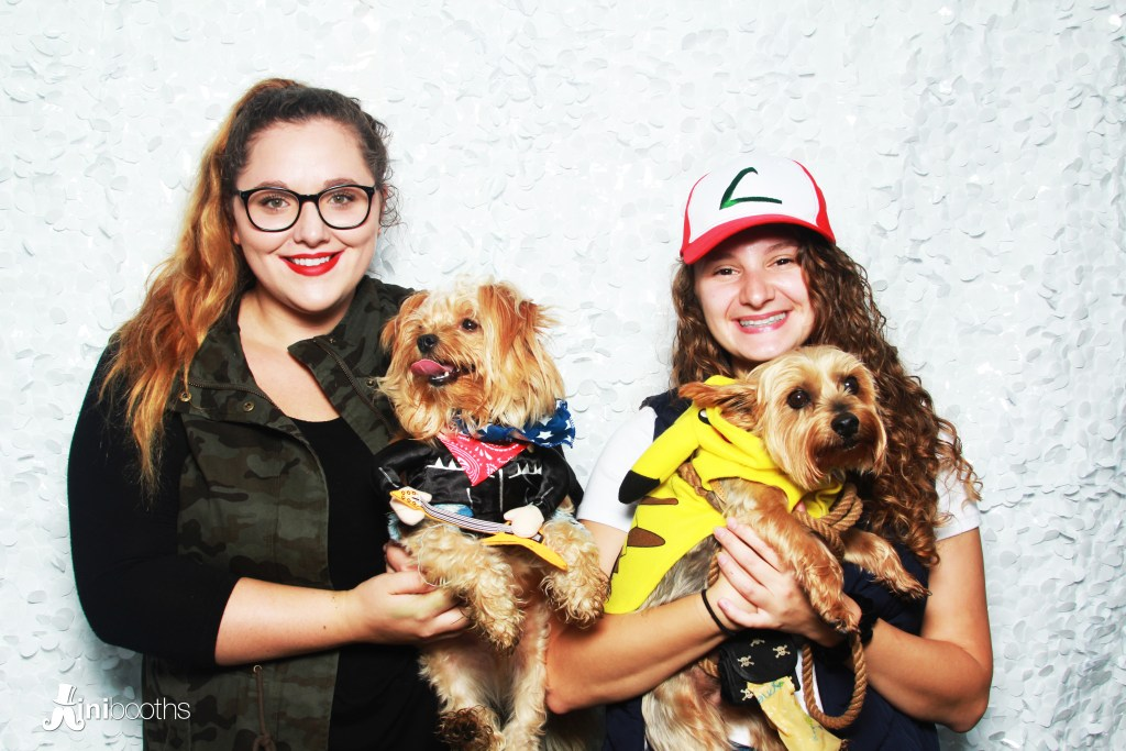 Two women each hold their own small dogs as they smile in a photobooth. One dog is dressed as a rockstar, the other is Pikachu.
