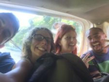 Four people crammed into the backseat of a minivan