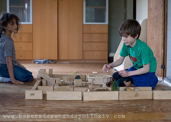 Avi and Tucker play with unit blocks and toy animals.