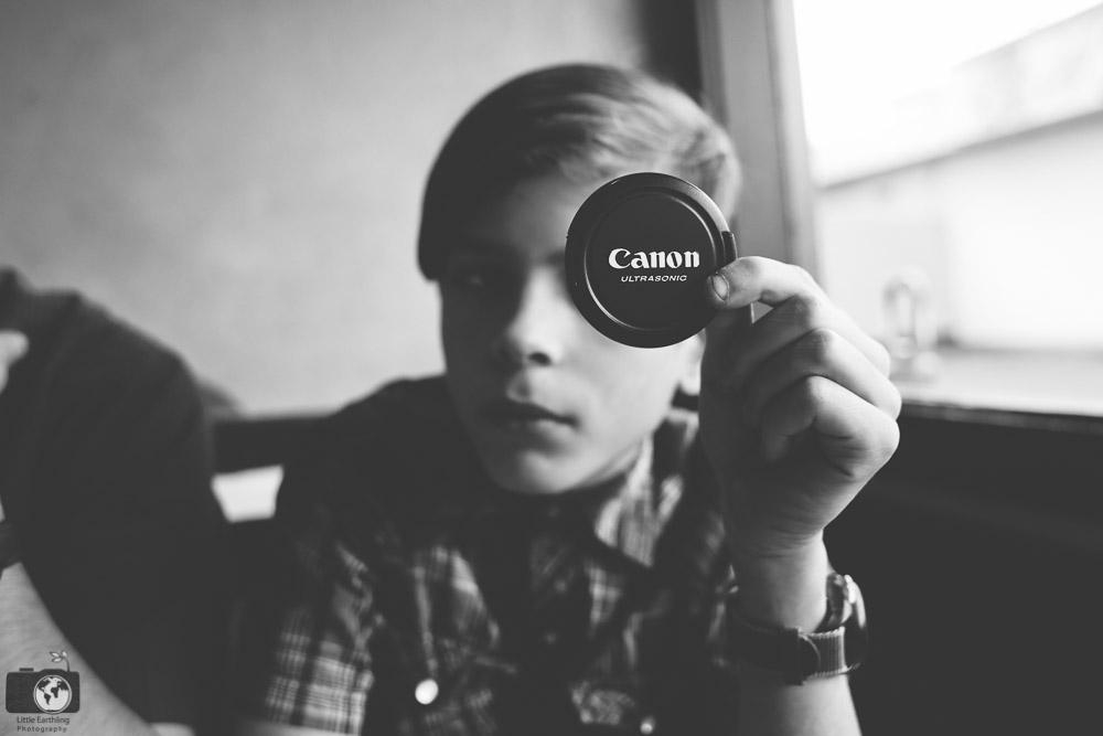 Holding a canon lens cap.