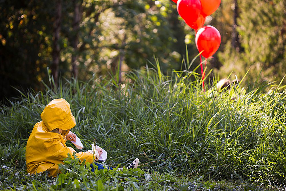 Little boy dressed as Georgie from It. Stephen King's It-themed photoshoot.