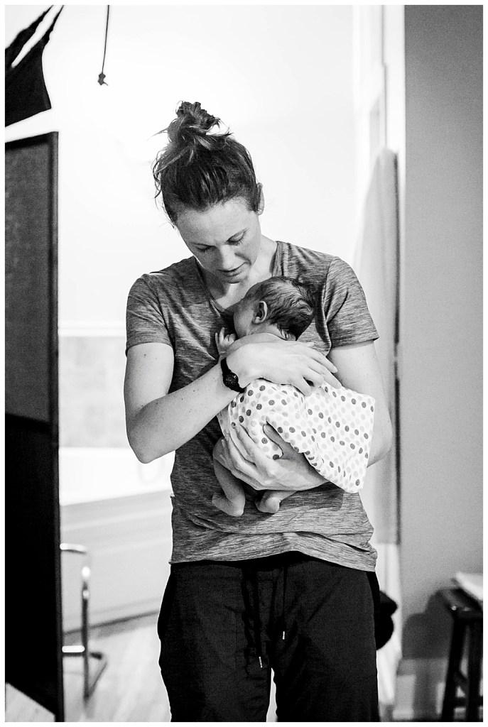 Bellingham midwife, Allie Watkins of Haven Midwifery, examines newborn after her birth.