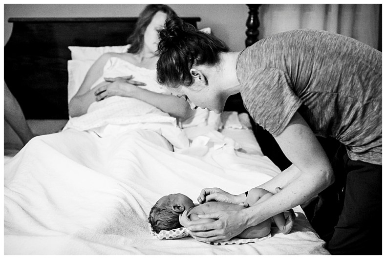 Bellingham midwife, Allie Watkins of Safehaven Midwifery, examines newborn after her birth.