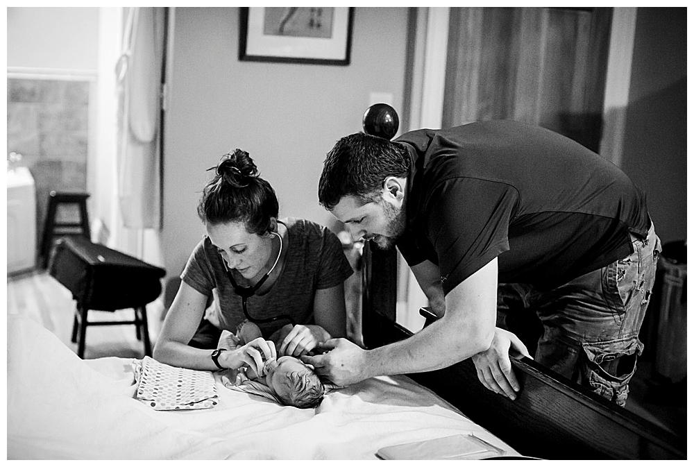 Bellingham midwife, Allie Watkins of Safehaven Midwifery, examines newborn after her birth.