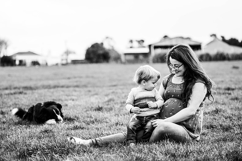 Black and white maternity photo with toddler and family dog.