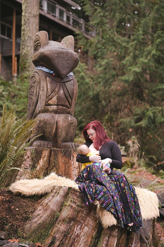 Mom breastfeeding baby outdoors in woods.