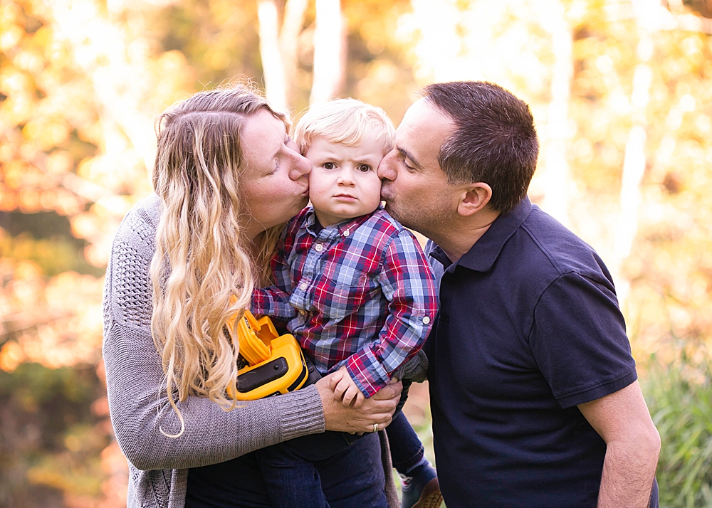 Mom and Dad kissing toddler. Bellingham family photography by Renee Bergeron.